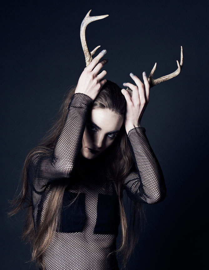 Dramatic portrait of girl holding deer antlers on her head