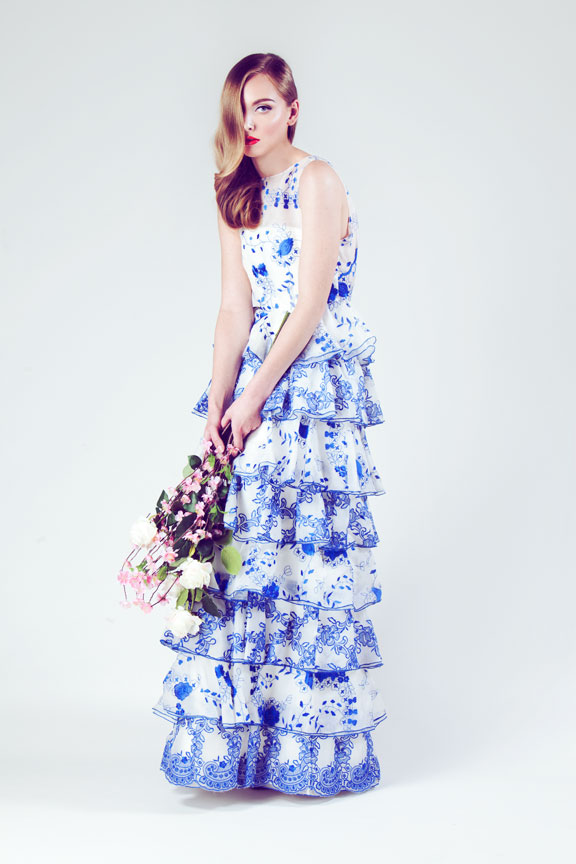Model holding flowers in floral print ruffle dress