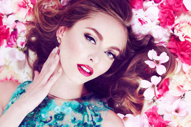 beauty image of Girl laying in pink flowers